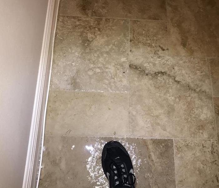 Water damage is shown on a tile floor