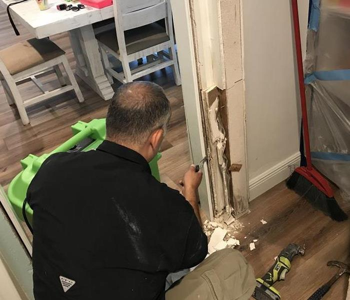 A SERVPRO of East Bradenton / Lakewood Ranch technician is shown removing mold damage