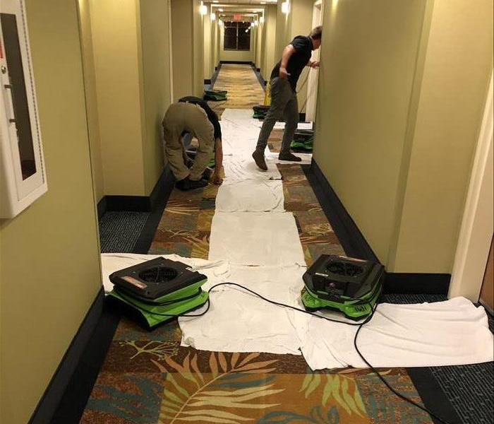 A flooded hotel hallway is shown with restoration equipment