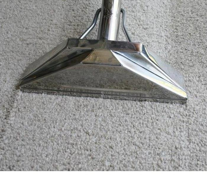 A carpet cleaning device is shown on a carpet