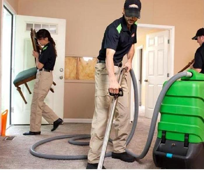 Three SERVPRO techncians are shown cleaning a carpet with SERVPRO equipment